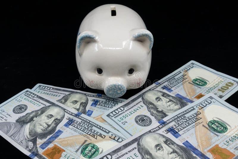 Primo piano isolato porcellino salvadanaio bianco su un mucchio di valuta degli Stati Uniti contro un fondo nero Ricchezza e conc fotografia stock libera da diritti