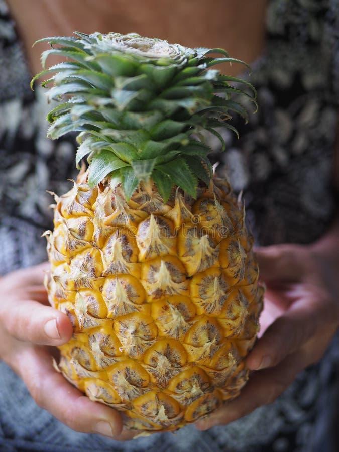 Primo piano l'ananas in mano della donna anziana immagini stock libere da diritti