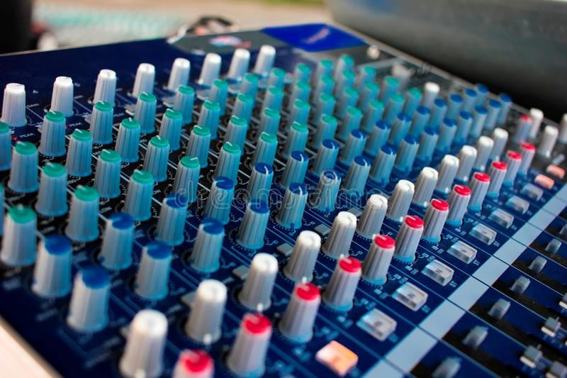 Primo piano laterale di una console di miscelazione con i cavi Audio miscelatore fotografia stock