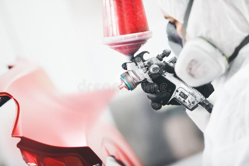 Primo piano, mano degli elementi della carrozzeria della pittura del riparatore nella camera della pittura fotografia stock libera da diritti
