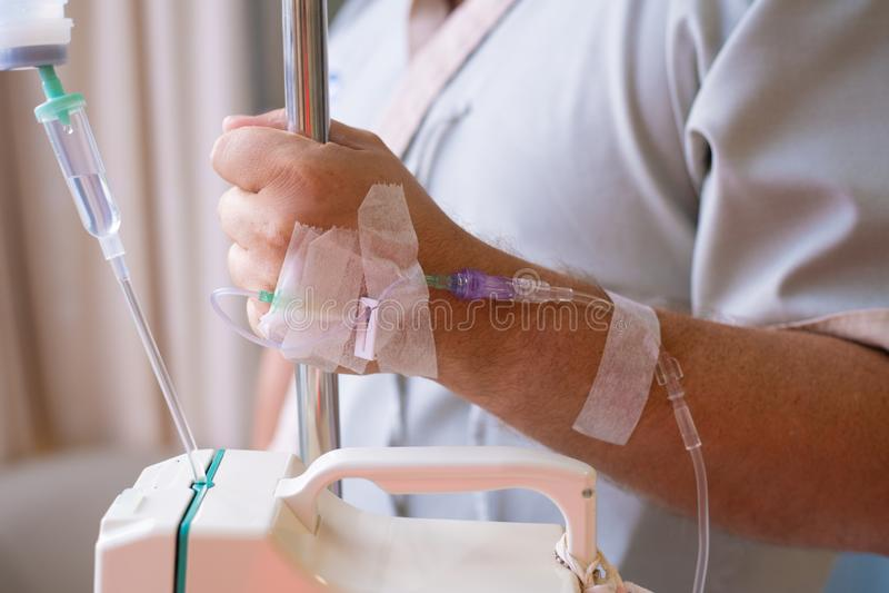 Primo piano Mano maschio con un contagoccia durante la chemioterapia in un ospedale Mano con un contagoccia La salute ? un argome fotografia stock