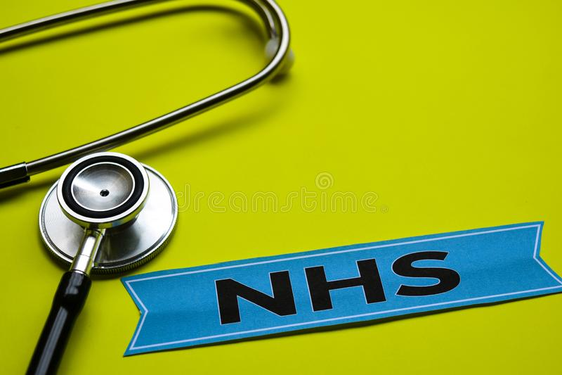 Primo piano NHS con ispirazione di concetto dello stetoscopio su fondo giallo fotografia stock