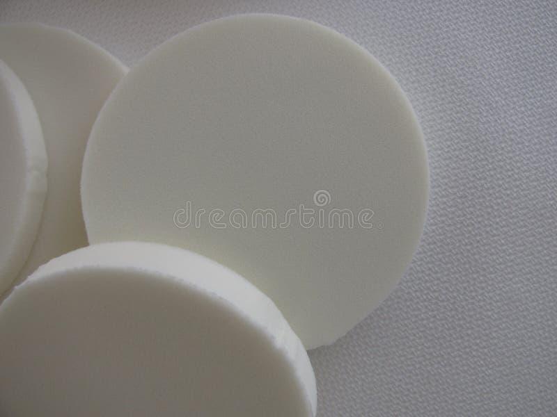 Primo piano orizzontale delle spugne bianche rotonde di trucco su fondo strutturato bianco con spazio per la copia immagine stock libera da diritti