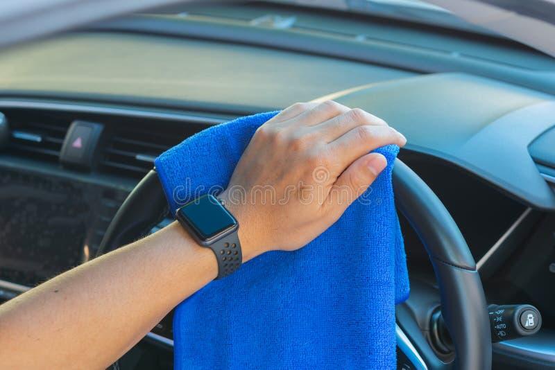 Primo piano per il volante di pulizia di lucidatura dell'automobile dell'uomo con il panno del microfiber immagini stock libere da diritti