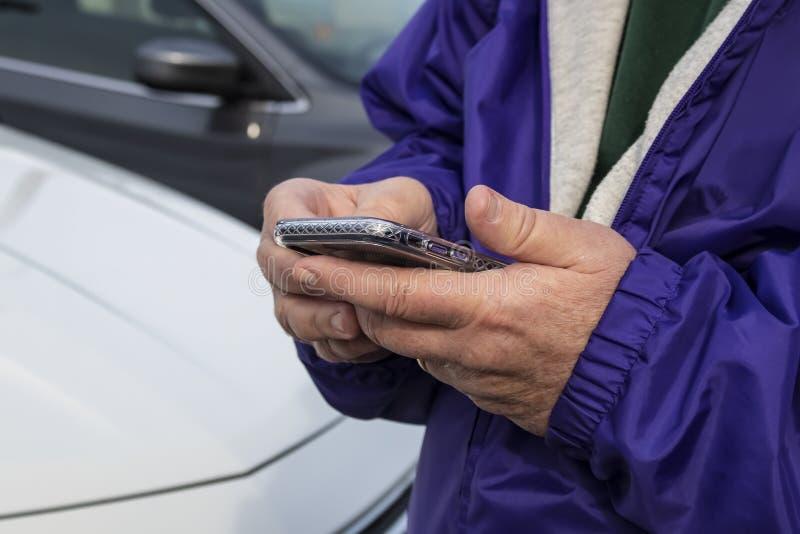 Primo piano potato dell'uomo in rivestimento porpora che tiene un telefono davanti alle automobili parcheggiate - fuoco selettivo fotografia stock
