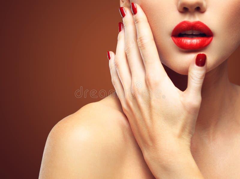 Primo piano sexy rosso dei chiodi e delle labbra Apra la bocca Manicure e trucco Componga il concetto fotografie stock libere da diritti