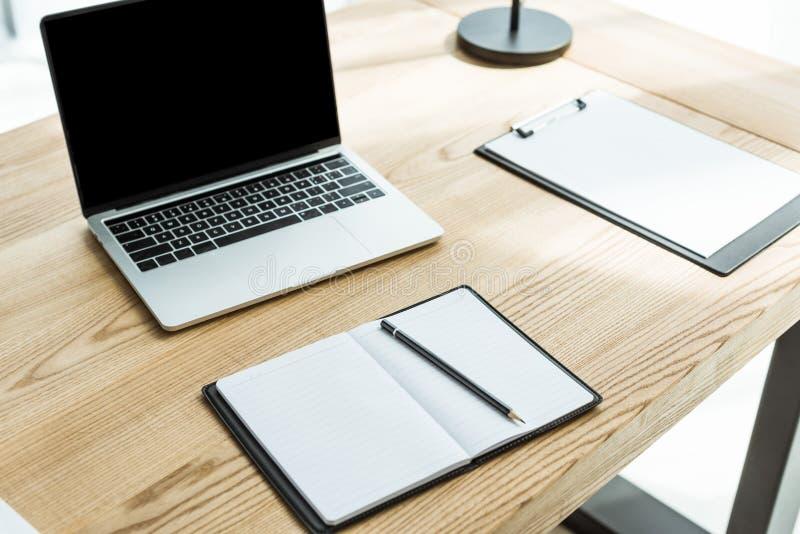 primo piano sparato del posto di lavoro moderno con il computer portatile e le carte in bianco fotografia stock libera da diritti