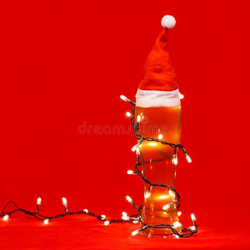 Primo piano sparato del vetro pieno di pilsner della birra o della birra inglese della birra chiara con Santa Claus o il cappello fotografia stock