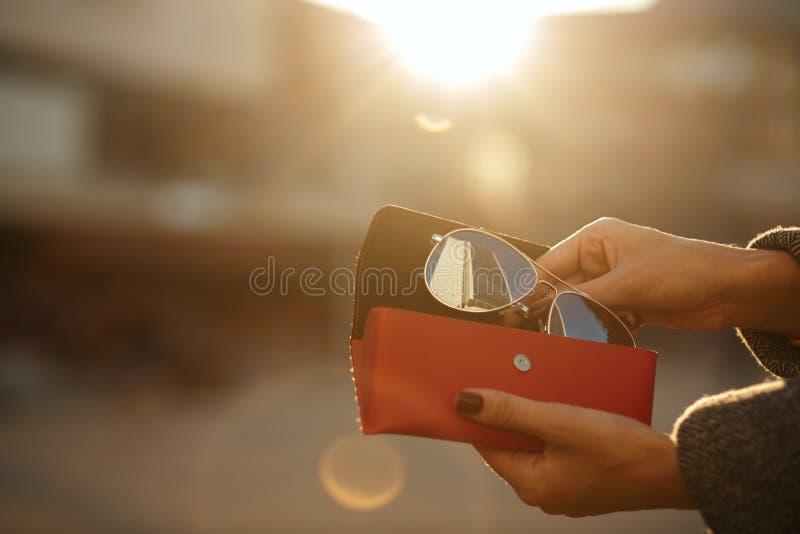 Primo piano sparato della cassa rossa di vetro di apertura femminile della mano alla parte posteriore fotografia stock libera da diritti