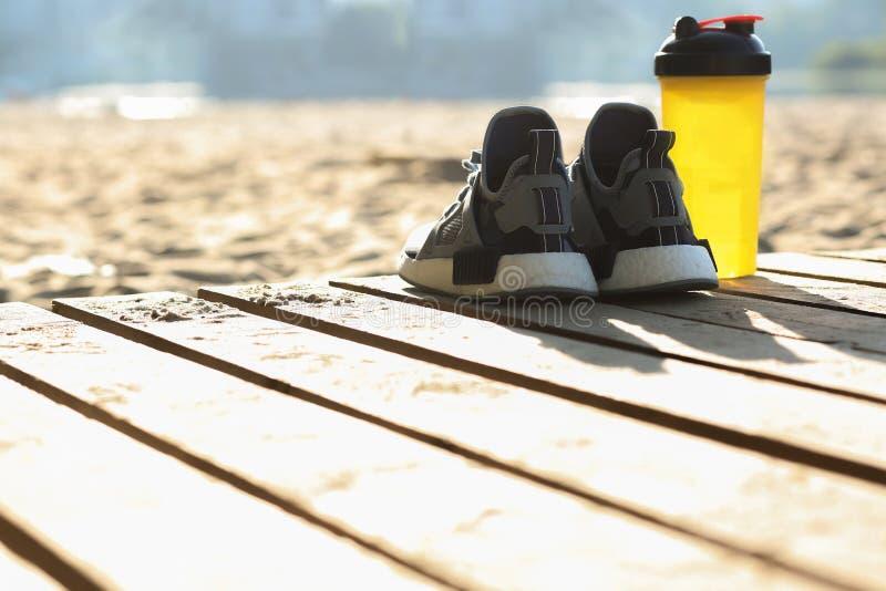 Primo piano sparato della condizione delle scarpe da tennis e della bottiglia di acqua della donna sulla spiaggia Spazio vuoto immagini stock