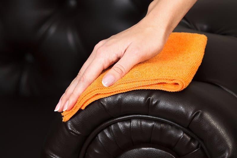 Primo piano sparato della mano femminile con le belle dita manicured che puliscono strato marrone fotografie stock