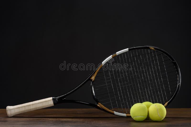 Primo piano sparato della racchetta di tennis e di tre palle disposte fotografia stock libera da diritti