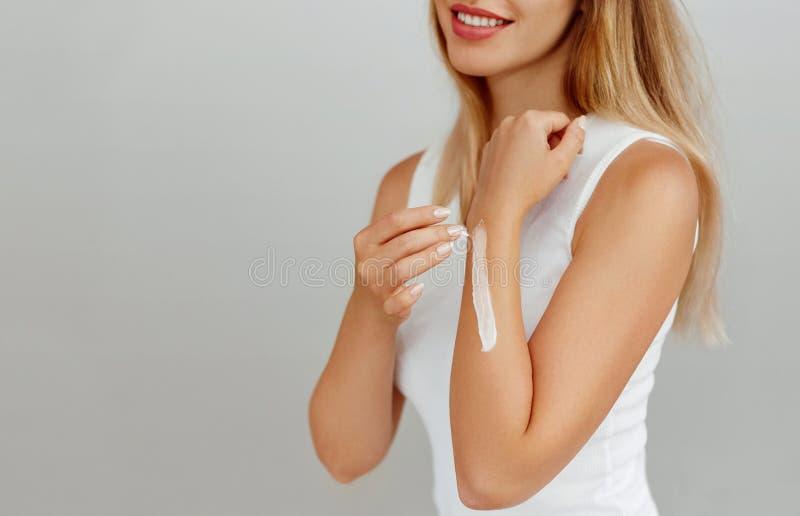 Primo piano sparato delle mani della donna che tengono crema e che applicano crema per le mani d'idratazione Belle mani femminili fotografie stock libere da diritti