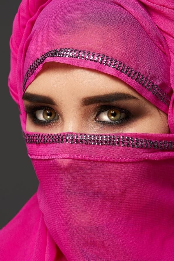 Primo piano sparato di giovane donna affascinante che indossa il hijab rosa decorato con gli zecchini Stile arabo fotografia stock