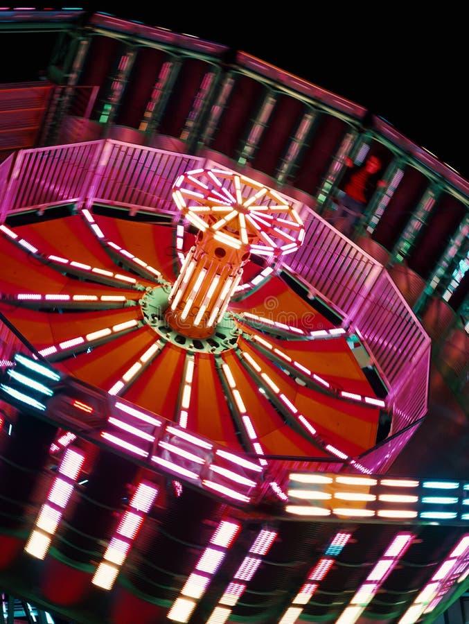 Primo piano sparato di un carosello di filatura ad un parco dell'attrazione durante il carnevale alla notte fotografia stock