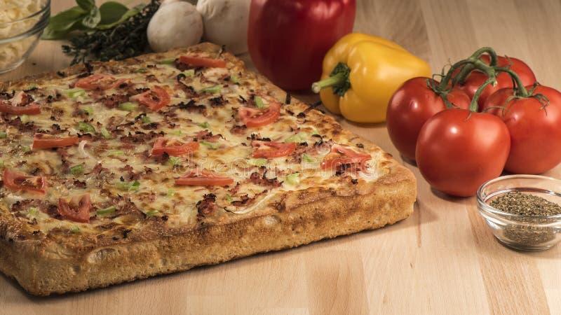 Primo piano sparato di una pizza a forma di quadrato con i pomodori, i peperoni, i funghi e le spezie freschi fotografie stock