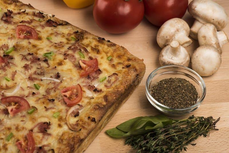 Primo piano sparato di una pizza a forma di quadrato con i pomodori, i peperoni, i funghi e le spezie freschi fotografia stock libera da diritti