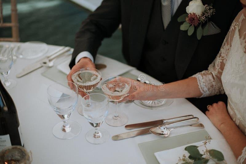 Primo piano sparato di una tenuta femminile e maschio due vetri di champagne su una tavola di nozze immagini stock