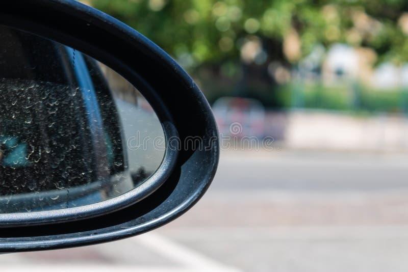 Primo piano sporco dello specchio del lato dell'automobile con l'immagine di sfondo della città fotografie stock libere da diritti