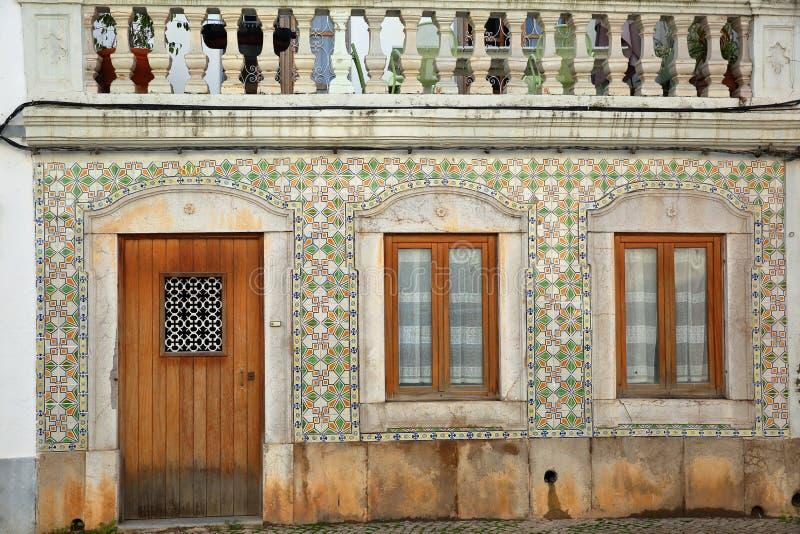 Primo piano su una facciata tipica della casa con i azulejos modellati delle mattonelle dentro la vecchia città di Tavira fotografie stock
