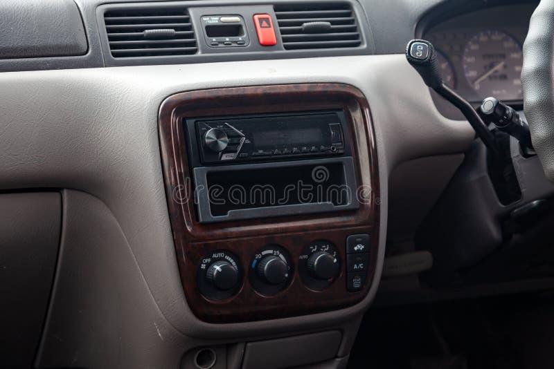 Primo piano sui bottoni di controllo di clima ed audio sistema all'interno di vecchia automobile giapponese in grigio dopo la pul immagini stock libere da diritti
