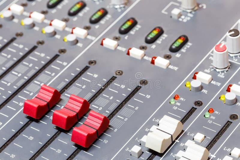 Primo piano sui cursori della console di mescolanza di suoni nell'audio registrazione immagini stock