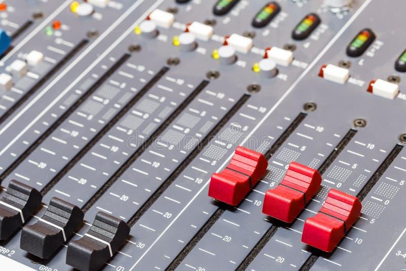 Primo piano sui cursori della console di mescolanza di suoni nell'audio registrazione immagine stock