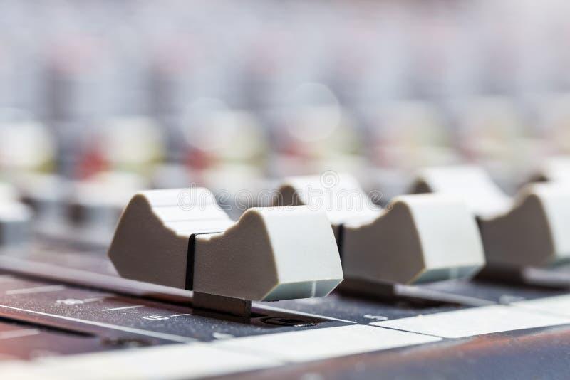 Primo piano sui cursori della console di mescolanza di suoni in st dell'audio registrazione fotografia stock libera da diritti