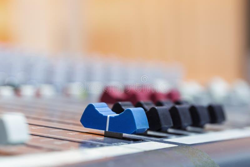 Primo piano sui cursori della console di mescolanza di suoni in st dell'audio registrazione immagini stock libere da diritti