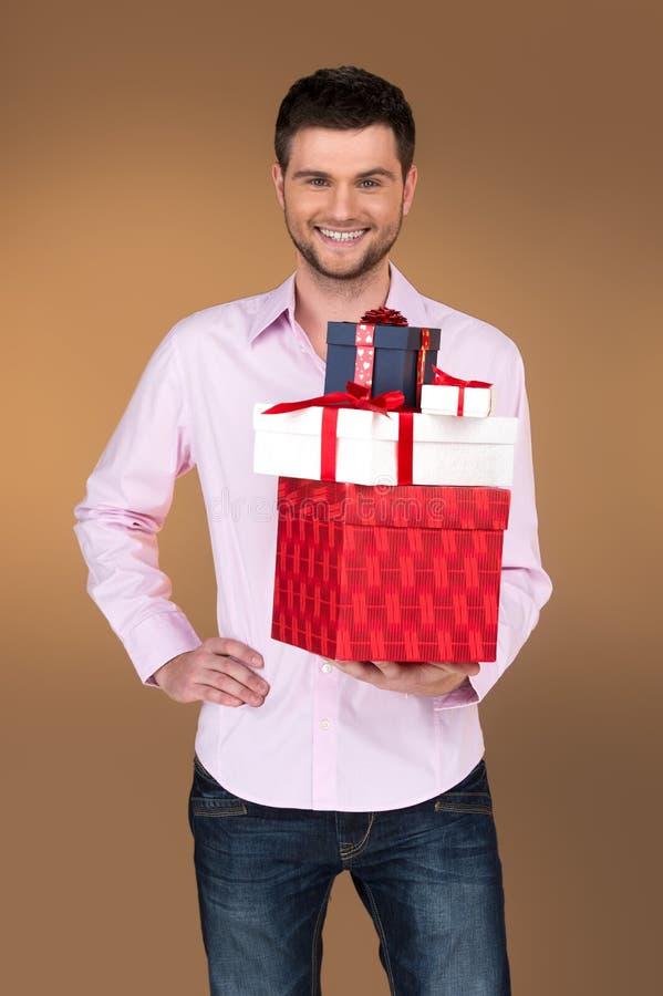 Primo piano sul tipo sorridente che tiene molte scatole immagini stock libere da diritti