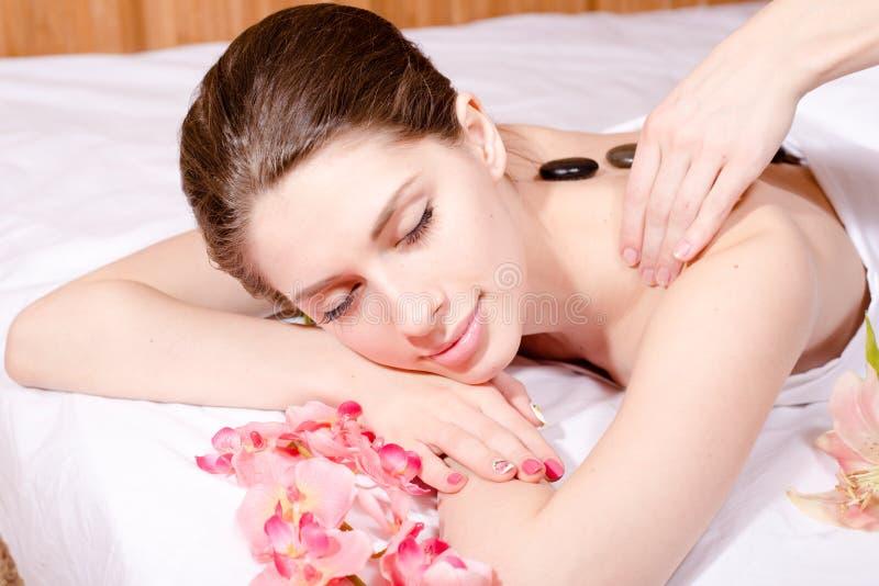 Primo piano sulla bella giovane donna che ha trattamenti della stazione termale: godere del massaggio, terapia delle pietre fotografia stock libera da diritti