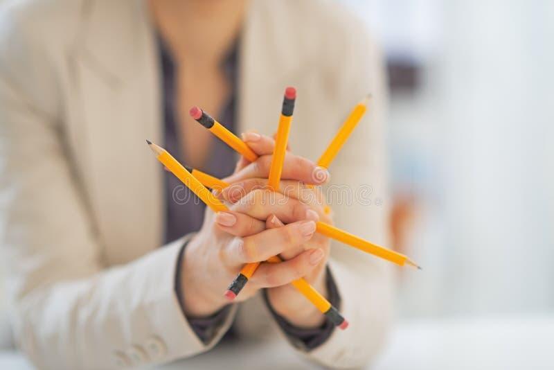 Primo piano sulla donna di affari che gioca con le matite immagini stock libere da diritti