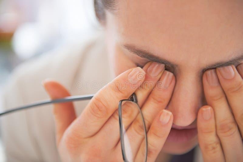 Primo piano sulla donna stanca di affari con gli occhiali fotografia stock libera da diritti