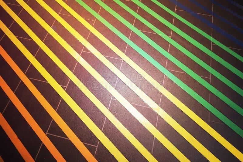 Primo piano sulla pavimentazione in piastrelle nera e sulle strisce variopinte parallele fotografie stock