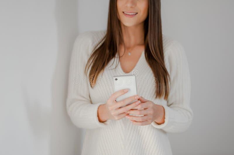 Primo piano sulle mani della donna facendo uso di uno smartphone fotografia stock libera da diritti