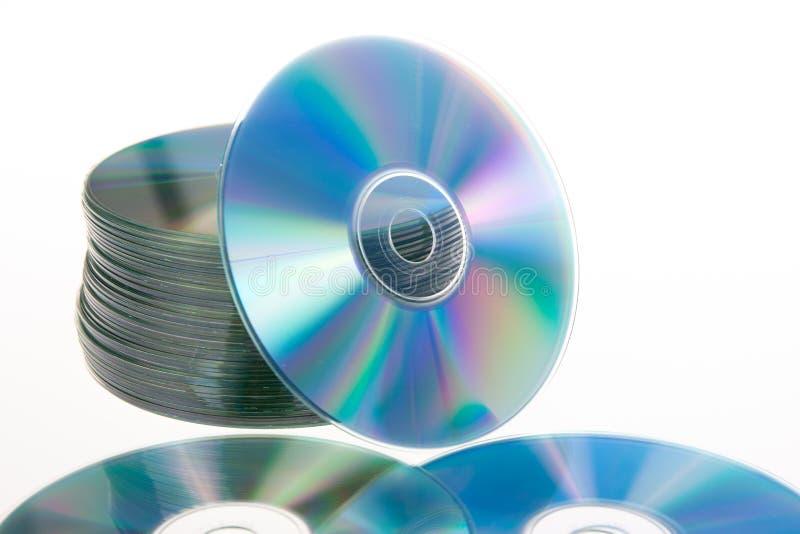 Primo piano tinto blu di una pila di CD di CD ROM che si trova sulla tavola bianca immagine stock
