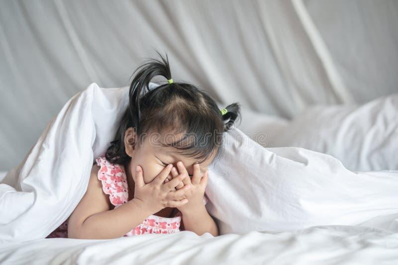 Primo piano una bambina prendere le sue mani fuori dal fronte e giocare nascosto con qualcuno sul letto sotto la coperta nel fond immagini stock libere da diritti