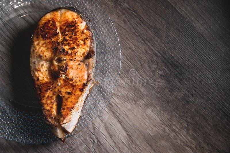 Primo piano uno grigliato con il trancio di pesce di color salmone di keta su un piatto trasparente di vetro su un fondo di legno immagine stock