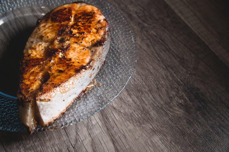 Primo piano uno grigliato con il trancio di pesce di color salmone di keta su un piatto trasparente di vetro su un fondo di legno fotografia stock