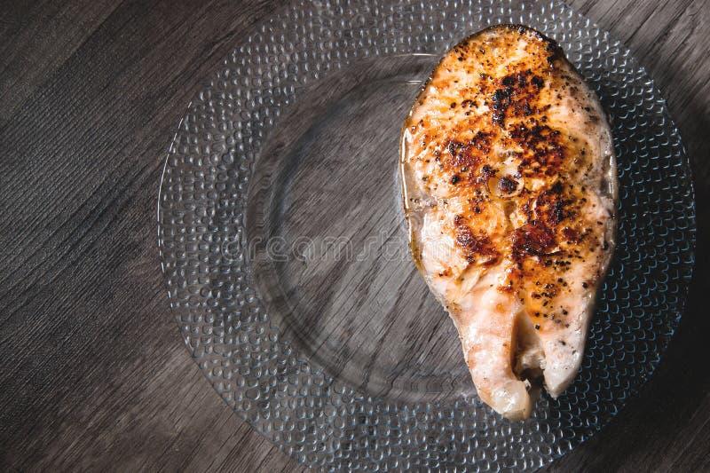 Primo piano uno grigliato con il trancio di pesce di color salmone di keta su un piatto trasparente di vetro su un fondo di legno immagini stock