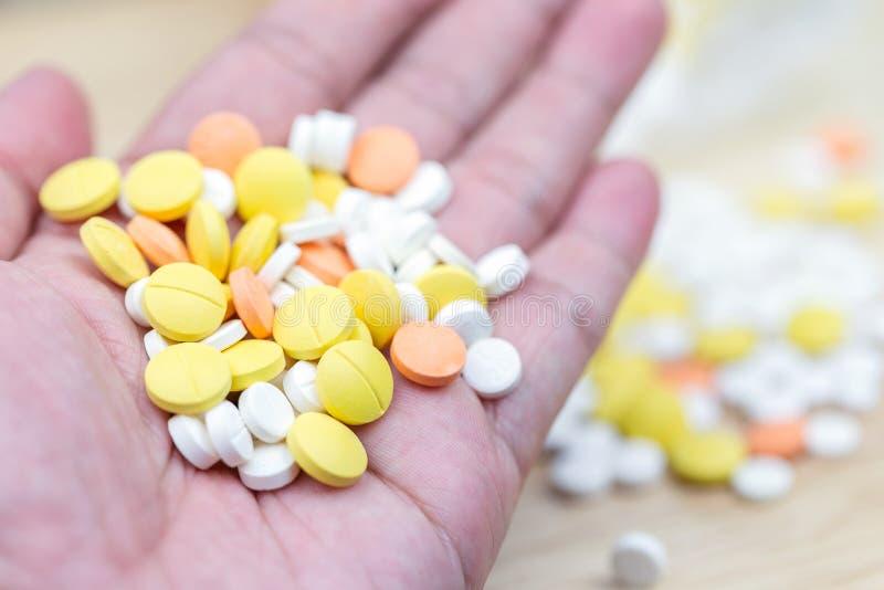 Primo piano variopinto delle compresse o delle droghe delle pillole della medicina a disposizione maschio immagine stock libera da diritti