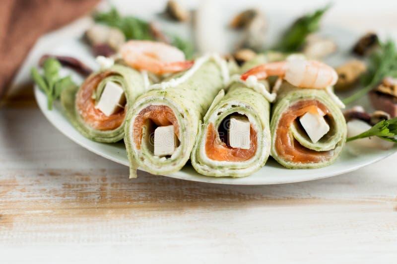 Primo piano verde dei pancake con il riempimento ed il formaggio del salmone fotografia stock