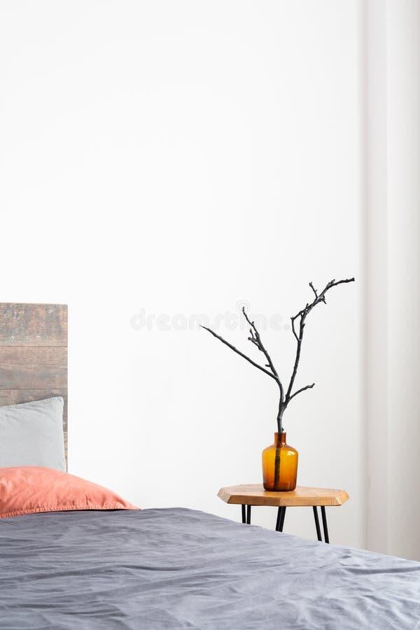 Primo piano verticale del vaso arancio di vetro con un ramo di albero che sta su una tavola di legno semplice accanto al letto fotografia stock libera da diritti