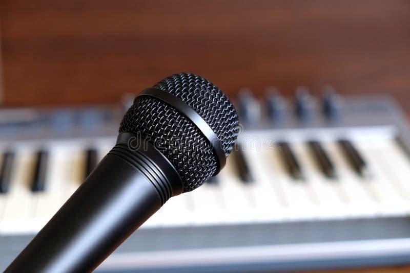 Primo piano vocale nero del microfono contro la tastiera elettronica del sintetizzatore fotografia stock