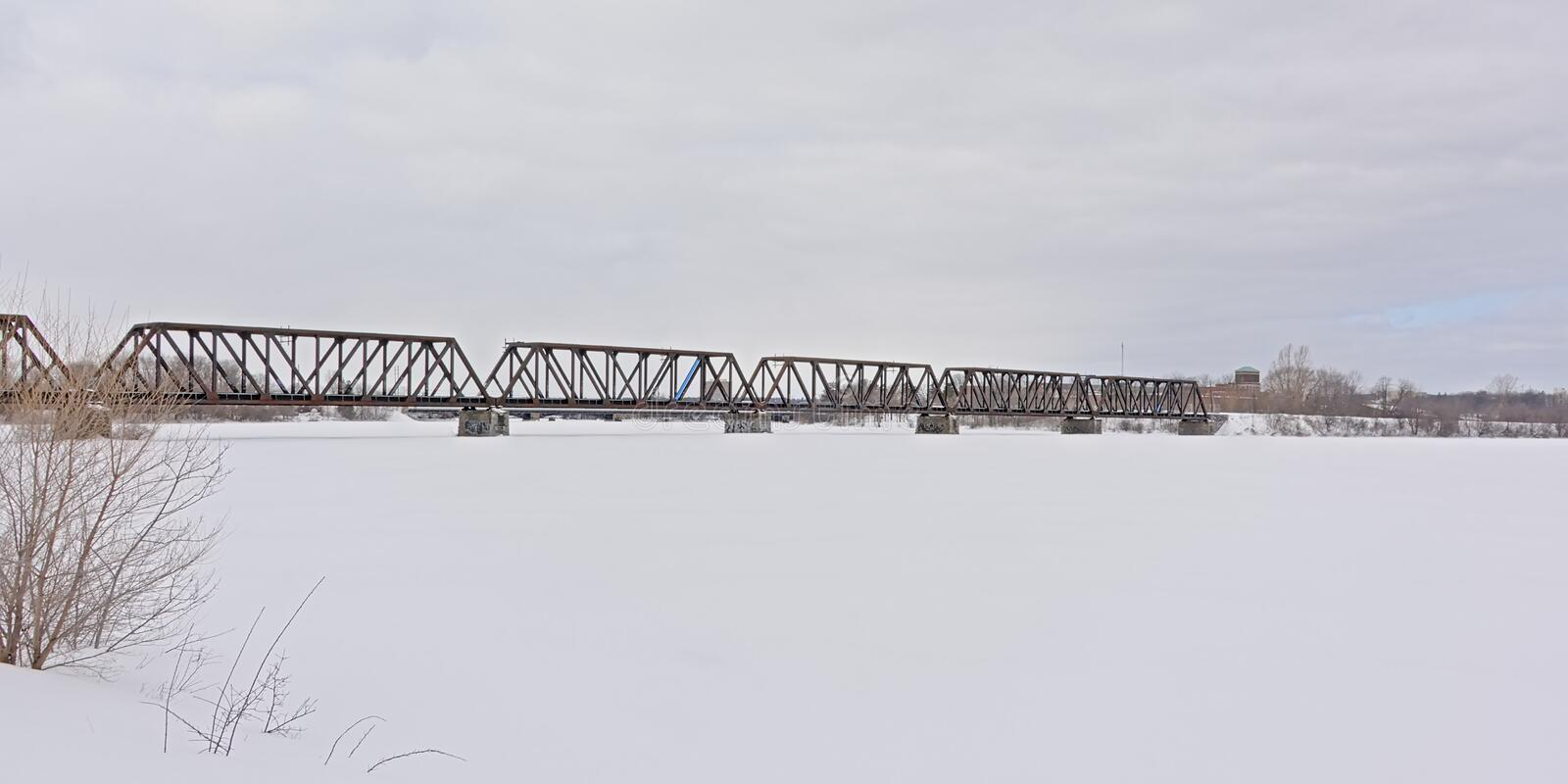 Prince of Wales rail bridge over frozen Ottawa river. On a cold winter day between  Ontario and Quebec i Canada stock images