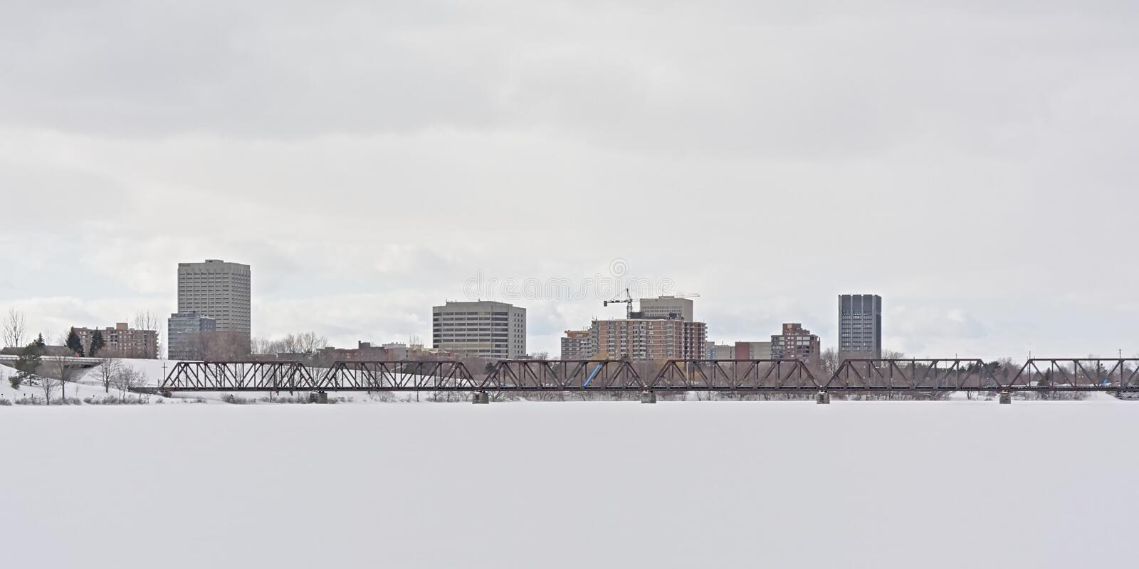 Prince of Wales rail bridge over frozen Ottawa river with office towers of Hull behind. Prince of Wales rail bridge over frozen Ottawa river on a cold winter day stock images