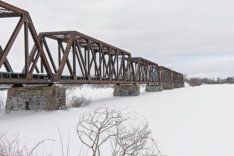 Prince of Wales rail bridge over frozen Ottawa river. On a cold winter day between  Ontario and Quebec i Canada royalty free stock images
