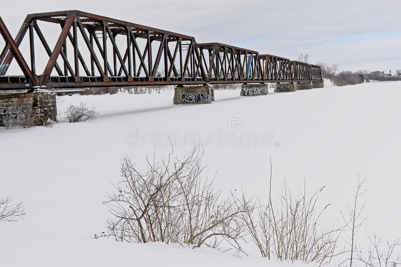 Prince of Wales rail bridge over frozen Ottawa river. On a cold winter day between Ontario and Quebec i Canada stock image