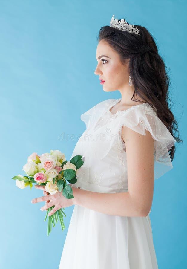 Princesa Bride em um vestido branco com uma coroa em um fundo azul imagem de stock