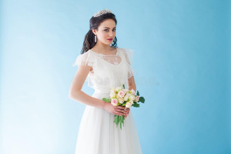 Princesa Bride em um vestido branco com uma coroa em um fundo azul imagem de stock royalty free